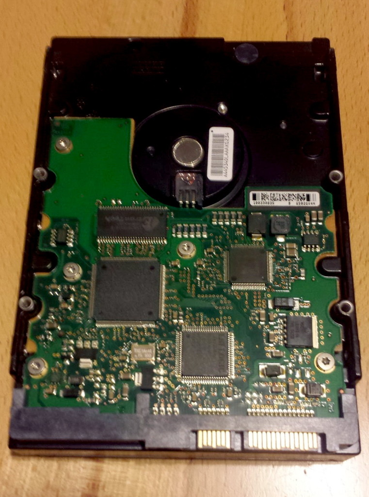 The green circuit board seen on the underside of this hard drive is the PCB board. The little black chips contain the firmware.
